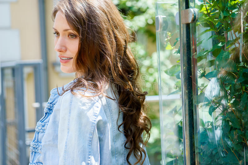 Brunette girl in profile with long wavy hair outdoors royalty free stock image