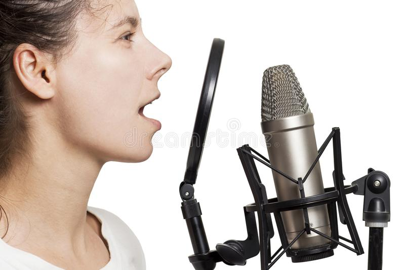 Brunette girl records voice to studio microphone. Young woman sings in studio condenser microphone with spider isolated. On white background. Write song in royalty free stock photos