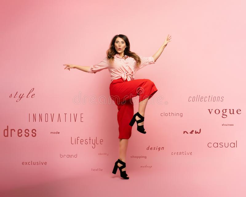Brunette girl with red clothes jumps over a pink background with fashion terms. Concept of fashion and shopping with. Brunette girl with red clothes jumps over a stock photos