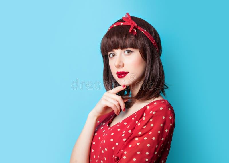 Brunette girl in red dress on blue background stock photo