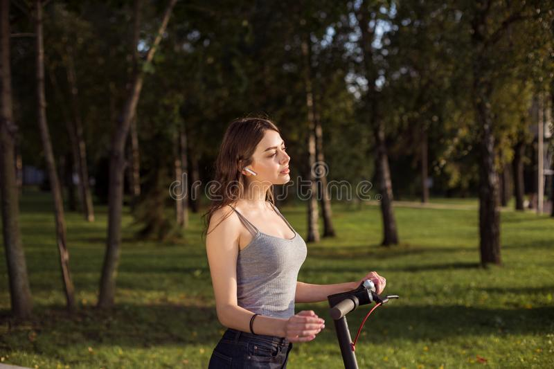 Brunette girl riding an eco-friendly electric kick scooter in a park in sunny weather on sidewalks stock photos