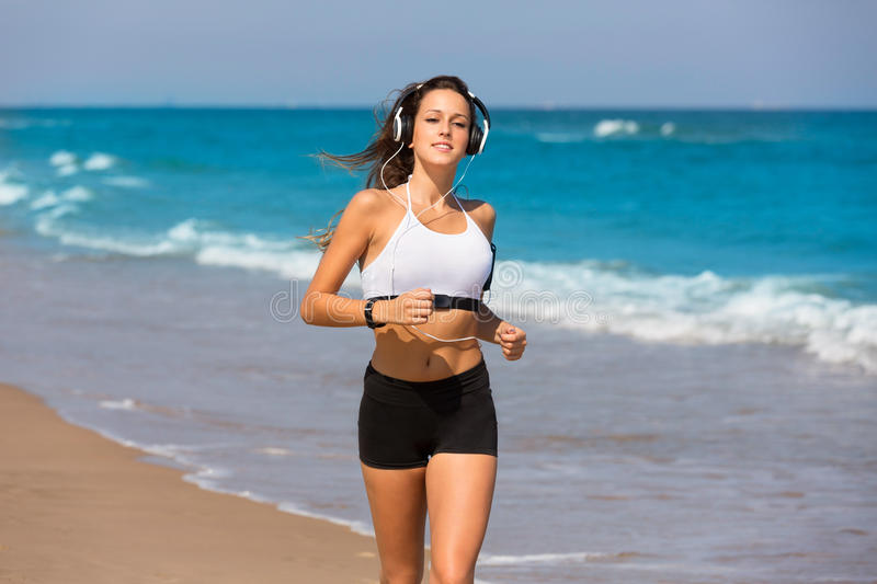 Brunette girl running on the beach headphones stock photography