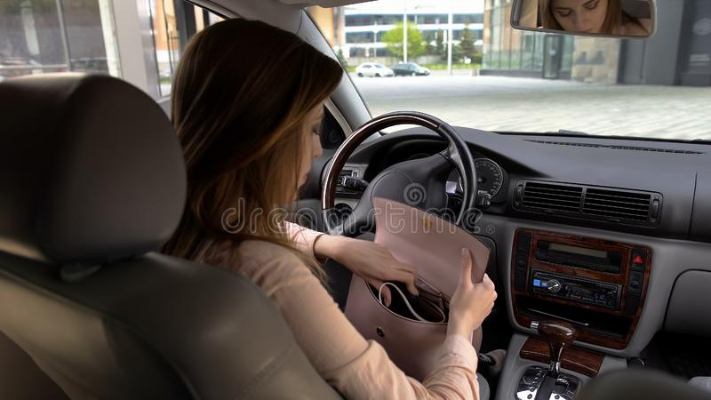 Brunette girl sitting in automobile and searching phone in her purse, back view royalty free stock photo