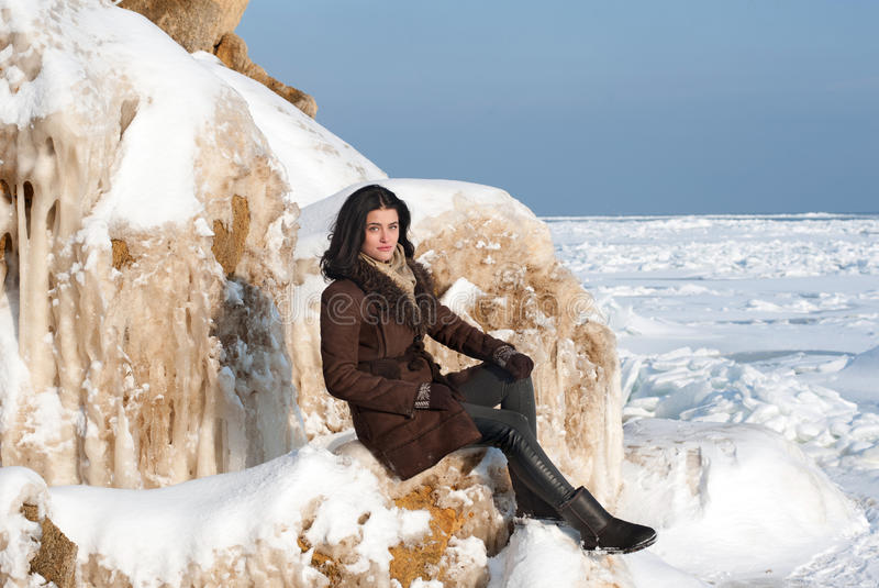 Brunette girl sitting on the ice-covered rock stock photos