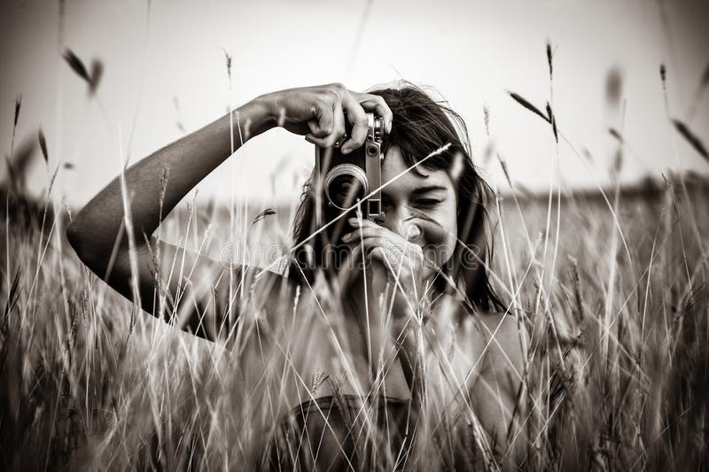 Brunette girl sitting at wheat field with camera. royalty free stock image