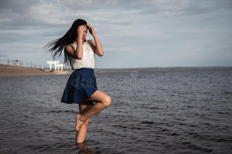 Brunette girl in a skirt standing in the water with her hair down. against the background of concrete and hydroelectric power. stock image