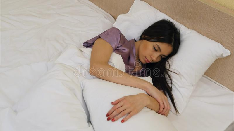 Brunette girl sleeping in bed moving and smiling in her sleep at home. Top view. Professional shot in 4K resolution. 068. You can use it e.g. in your stock photography