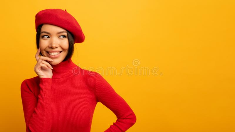 Brunette girl smiles with red hat and cardigan. Emotional and joyful expression. Yellow background. Brunette cute girl smiles with red hat and cardigan royalty free stock photos