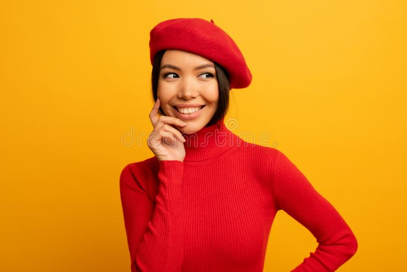 Brunette girl smiles with red hat and cardigan. Emotional and joyful expression. Yellow background stock photo