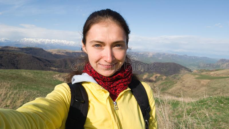 Brunette girl takes a selfie on a smartphone on the background of the field and mountains. On the shoulders of the backpack. stock photo