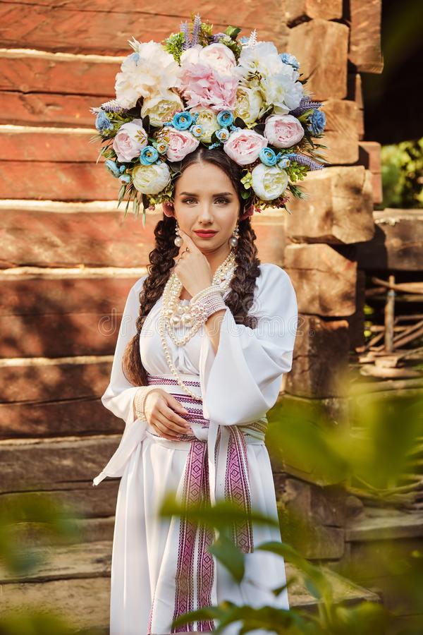 Brunette girl in a white ukrainian authentic national costume and a wreath of flowers is posing against a wooden house. Beautiful brunette girl with a long dark royalty free stock photography