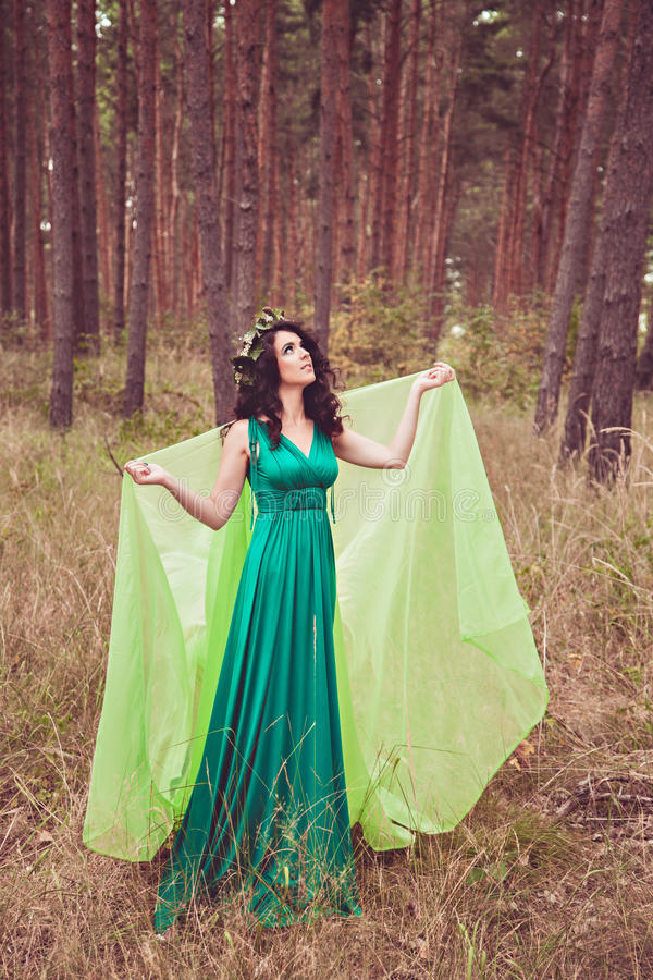 Brunette girl with wreath and in green dress royalty free stock images