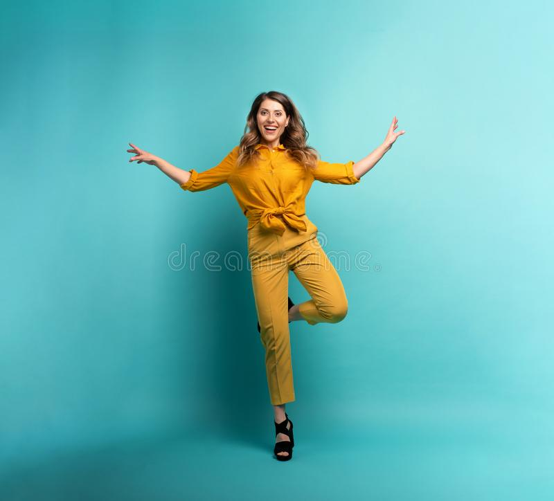 Brunette girl with a yellow clothes jumps over a cyan background. Concept of fashion and shopping with joyful expression. Brunette girl with a yellow clothes stock photo