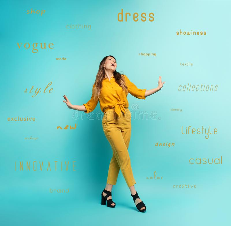 Brunette girl with a yellow clothes walks over a cyan background. Concept of fashion and shopping with joyful expression. Brunette girl with a yellow clothes royalty free stock photos