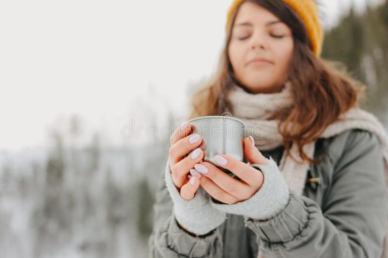 Brunette girl in yellow knitted hat with metal mug of hot tea in the forest outdoors in winter, selective focus stock photos