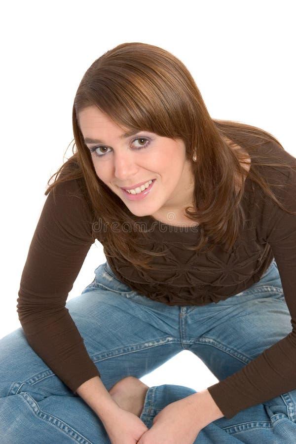 Brunette grazioso che si siede a gambe accavallate fotografia stock libera da diritti