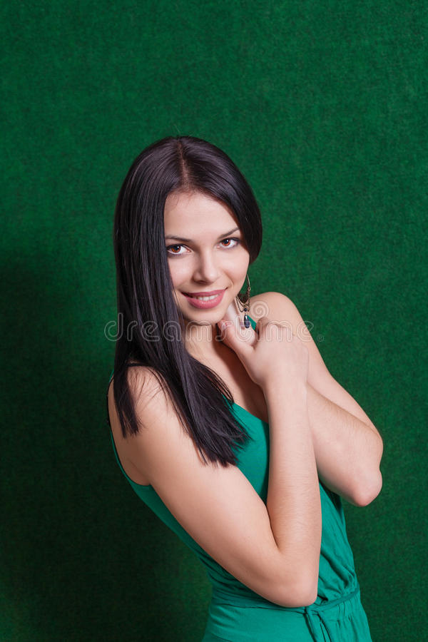 Brunette in groene kleding tegen muur stock afbeeldingen