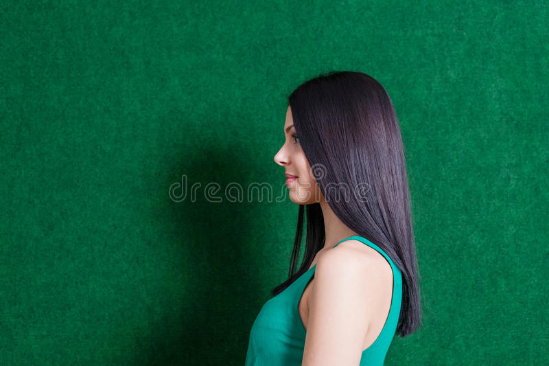 Brunette in groene kleding tegen muur royalty-vrije stock fotografie