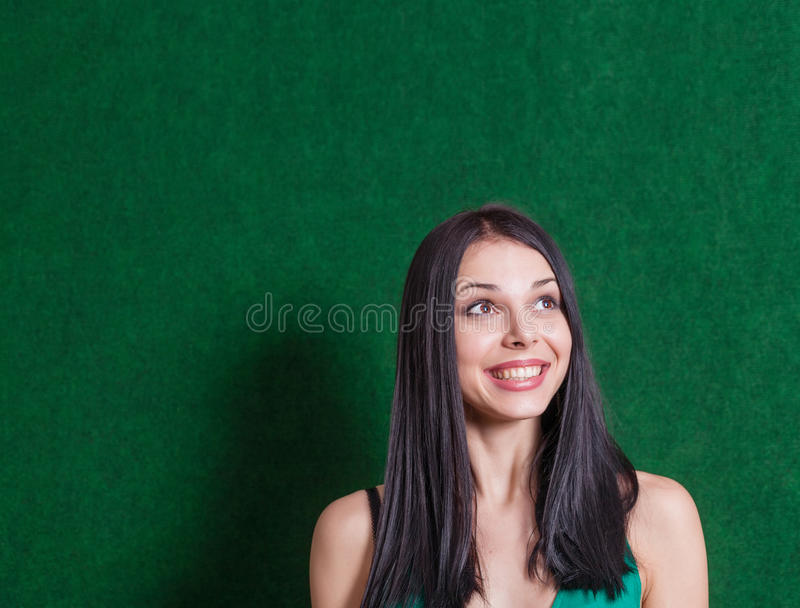 Brunette in groene kleding tegen muur royalty-vrije stock afbeeldingen