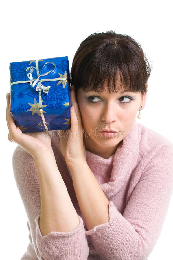 Brunette guessing what is in the present. Young brunette with blue Christmas present isolated over white stock images