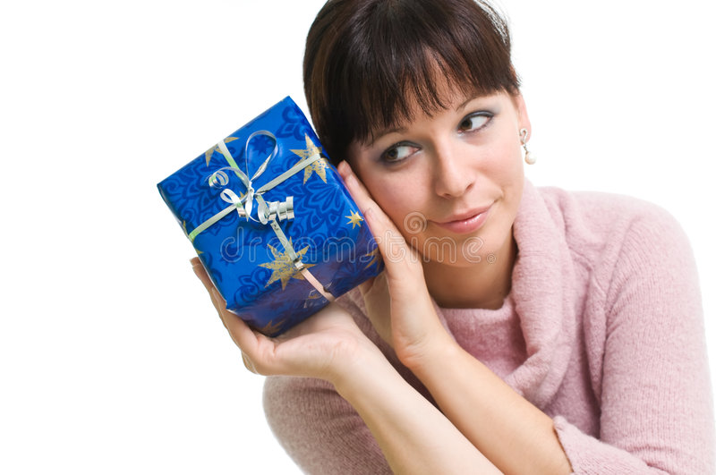 Brunette guessing what is in the present. Young brunette with blue Christmas present isolated over white royalty free stock photos