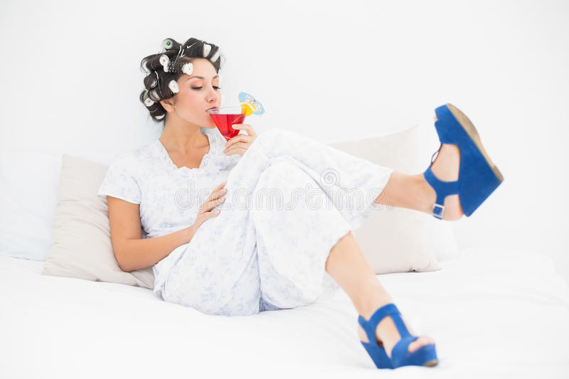 Brunette in hair rollers and wedge shoes drinking a cocktail