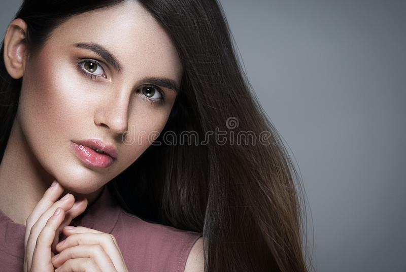 Brunette hair woman. Beautiful brunette hairstyle fashion portrait with beauty long black hair over gray background stock photo