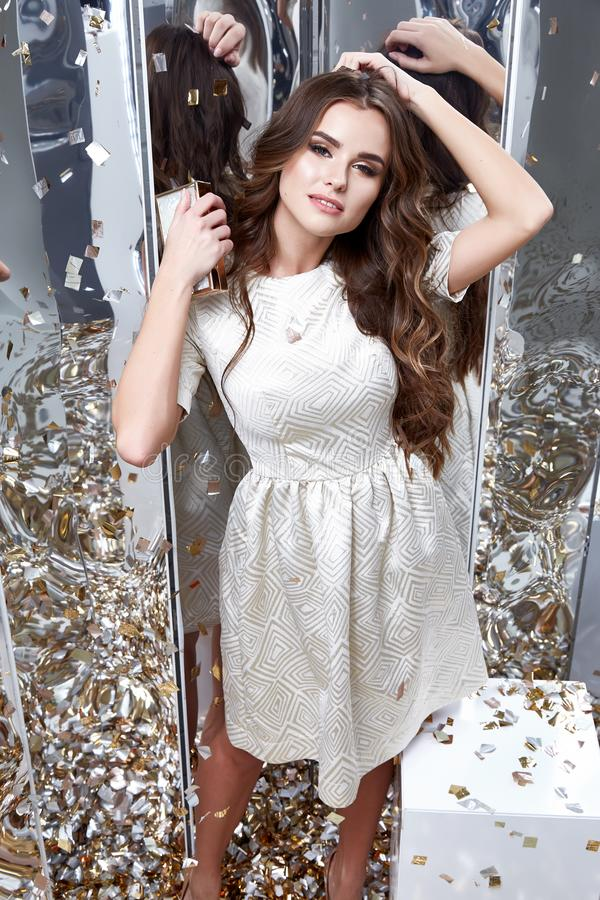 Brunette hair woman wear fashion white dress party style pretty. Beautiful face model pose catalog of fashion clothes celebrate mirror sequins background studio royalty free stock photos