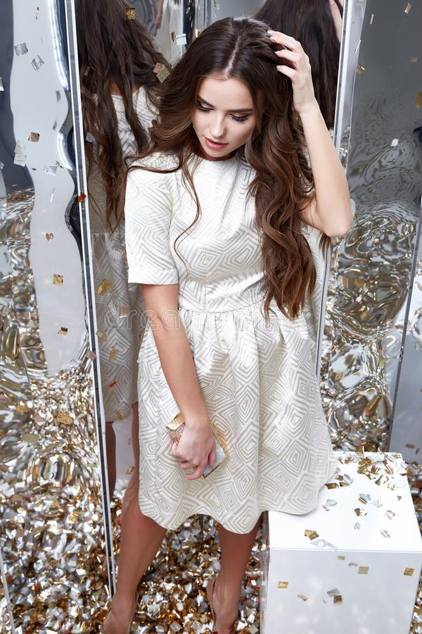 Brunette hair woman wear fashion white dress party style pretty. Beautiful face model pose catalog of fashion clothes celebrate mirror sequins background studio stock image