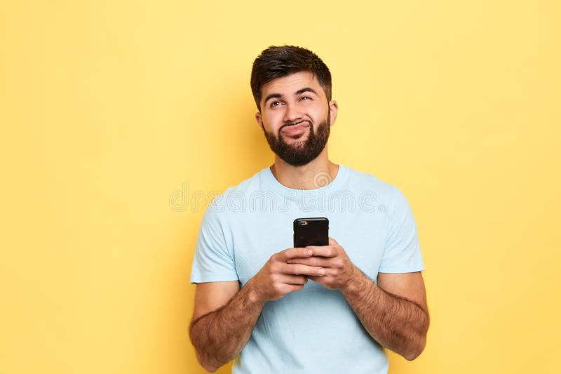 Brunette handsome puzzled man using smartphone isolated over yellow background royalty free stock photo