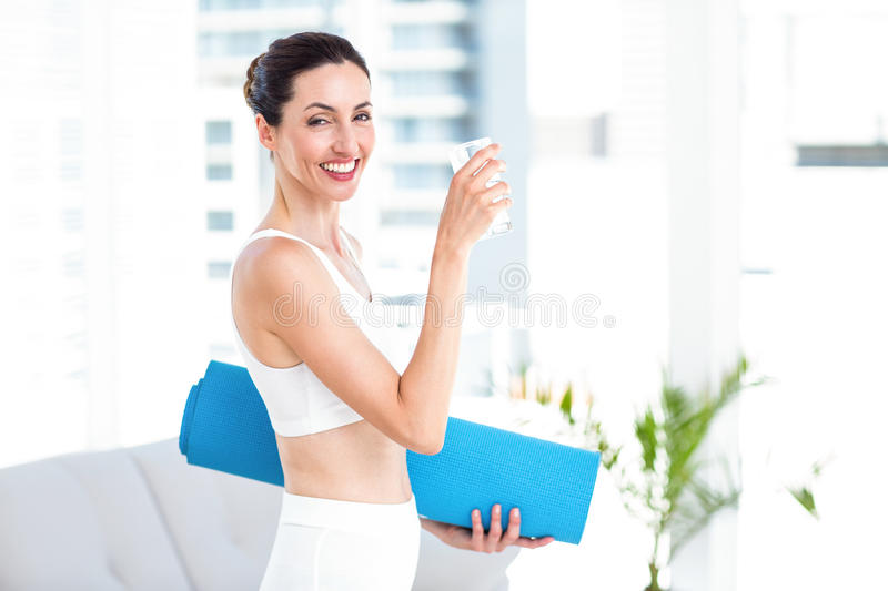 Brunette holding glass of water and exercise mat stock images