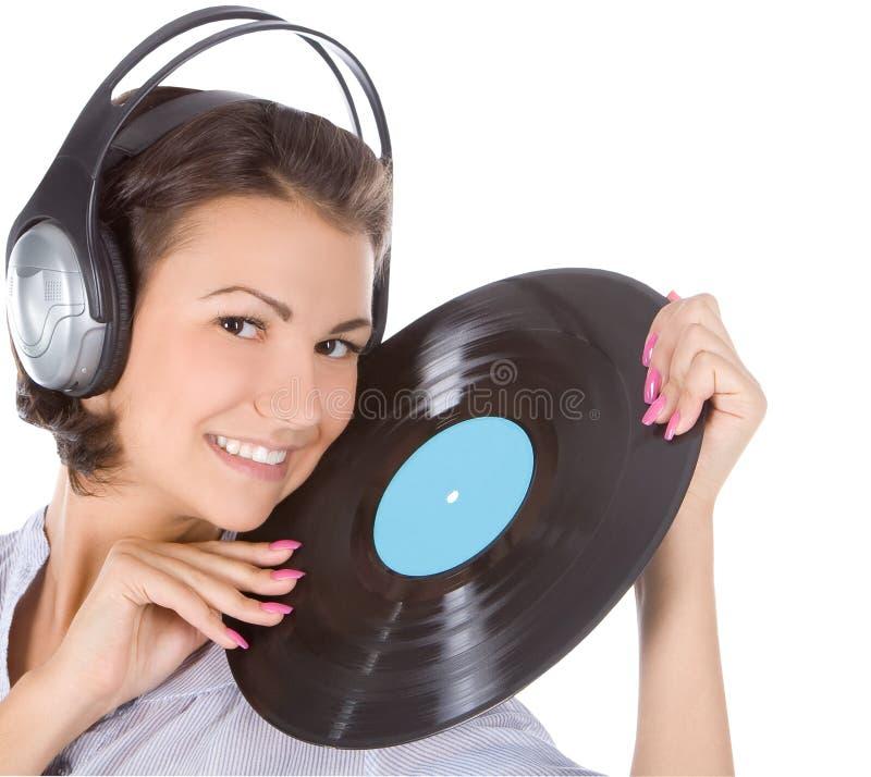 Brunette in hoofdtelefoons met vinylverslag stock afbeelding
