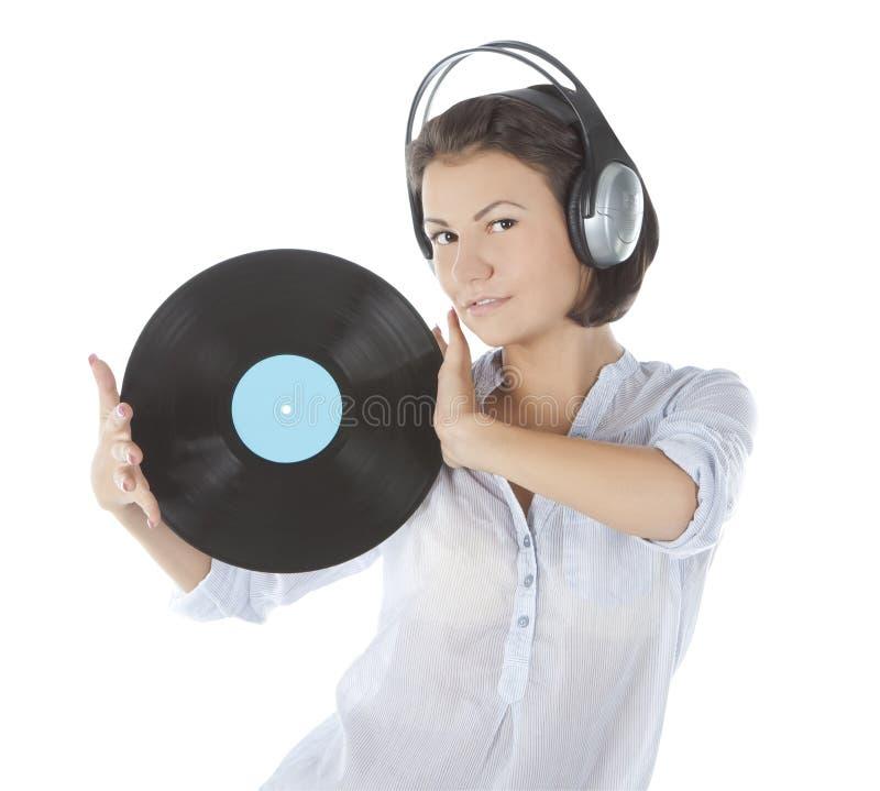 Brunette in hoofdtelefoons met vinylverslag stock foto