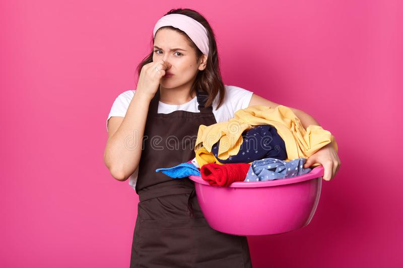 Brunette houseworker holding her nose with one hand, having full pink basin of bad smelling items of clothes, trying to bear smell royalty free stock image