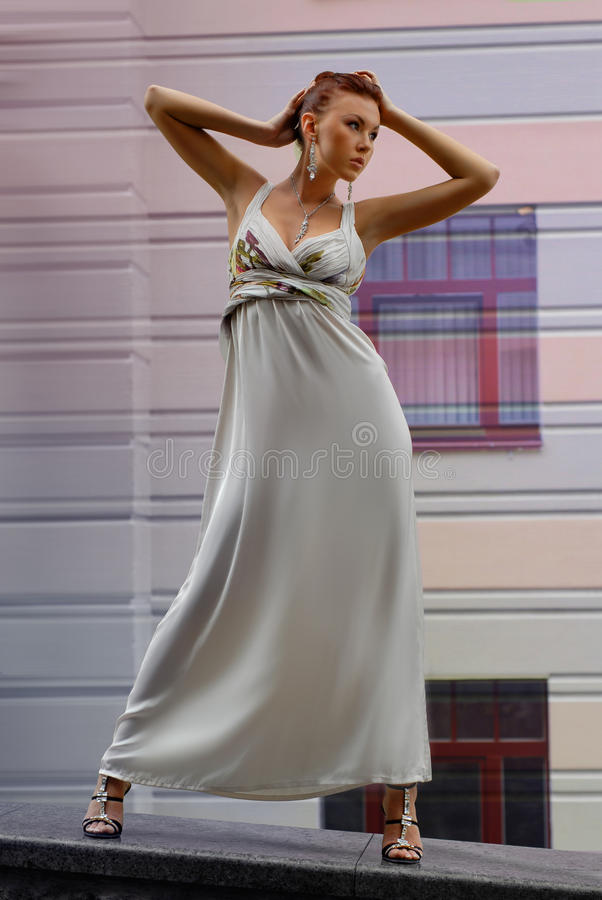 Brunette im langen Kleid nahe einem Hotel stockbild