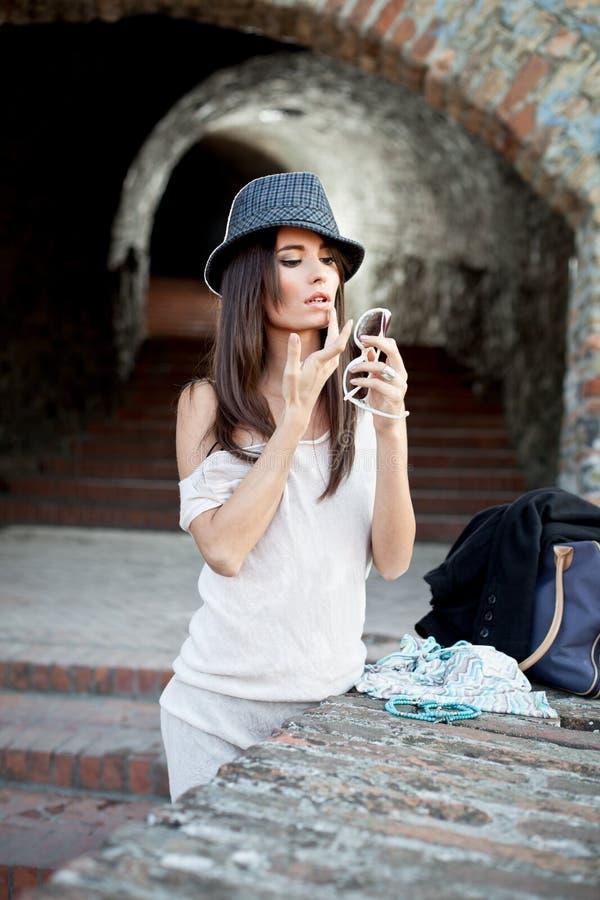 Brunette joven atractivo con la presentación del sombrero. imagenes de archivo
