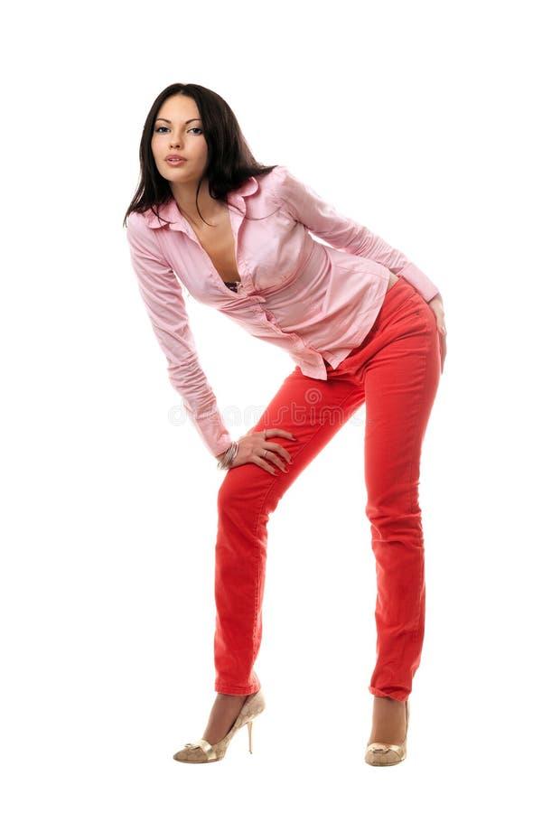 Brunette joven juguetón en pantalones vaqueros rojos imágenes de archivo libres de regalías