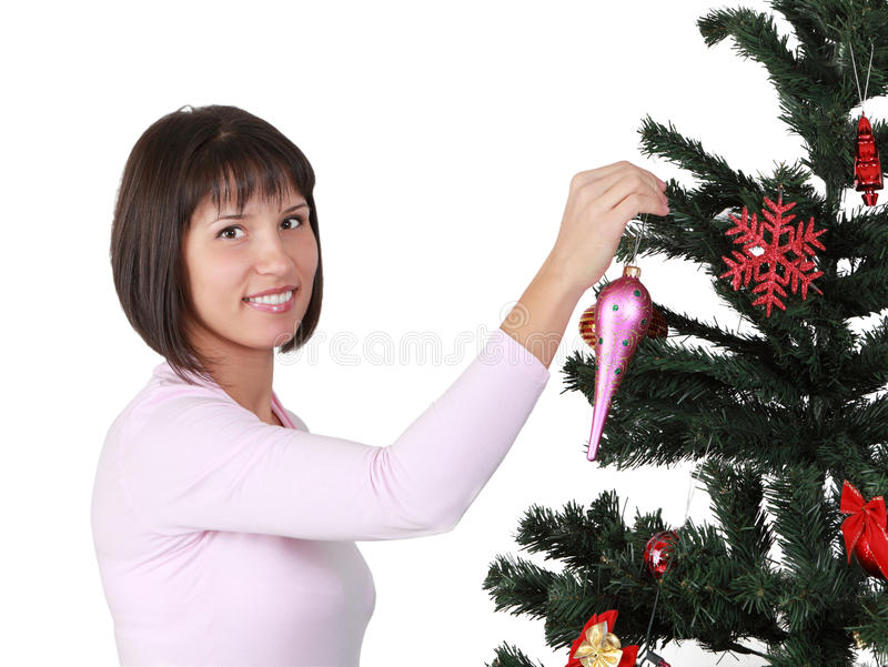 Brunette joven que adorna el árbol de navidad