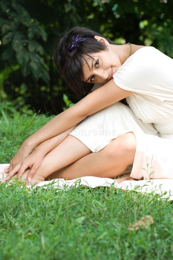 Brunette joven sensual que se sienta en hierba imagenes de archivo