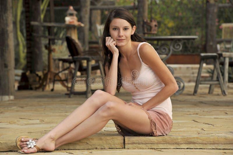 Brunette-jugendlich Sitzen auf Patio lizenzfreie stockbilder