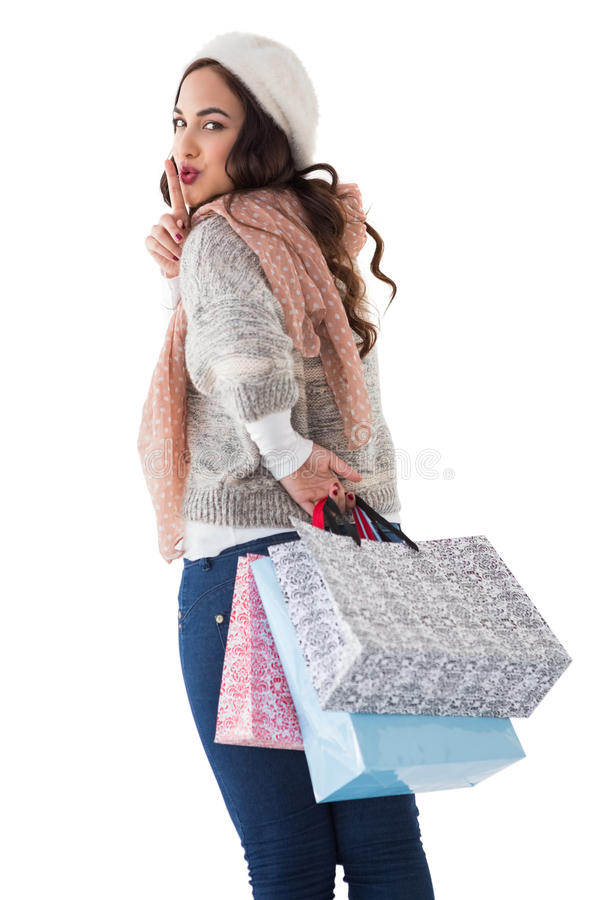 Brunette keeping a secret and holding shopping bags royalty free stock photography