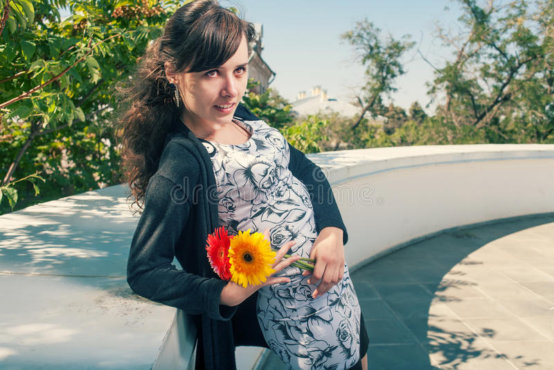 Brunette in kledingshelling tegen een muur met bos van bloemen in h royalty-vrije stock foto