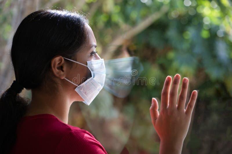 Brunette kvinna med en ansiktsmask som ser genom fönstret med sin reflektion på glaset Konceptet Coronavirus och kvarentine royaltyfri fotografi