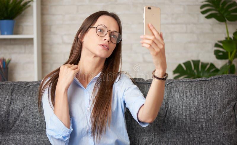 Brunette-kvinnan tar selfie på sin smartphone arkivbild