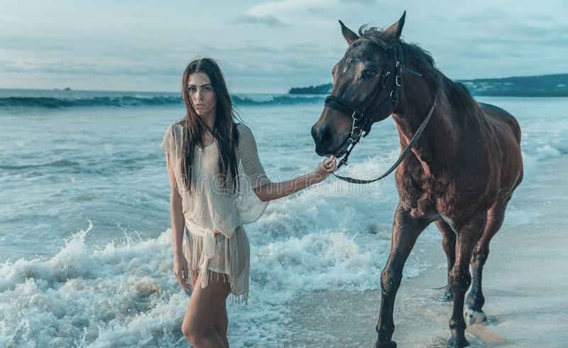 Brunette lady walking with a horse stock photos