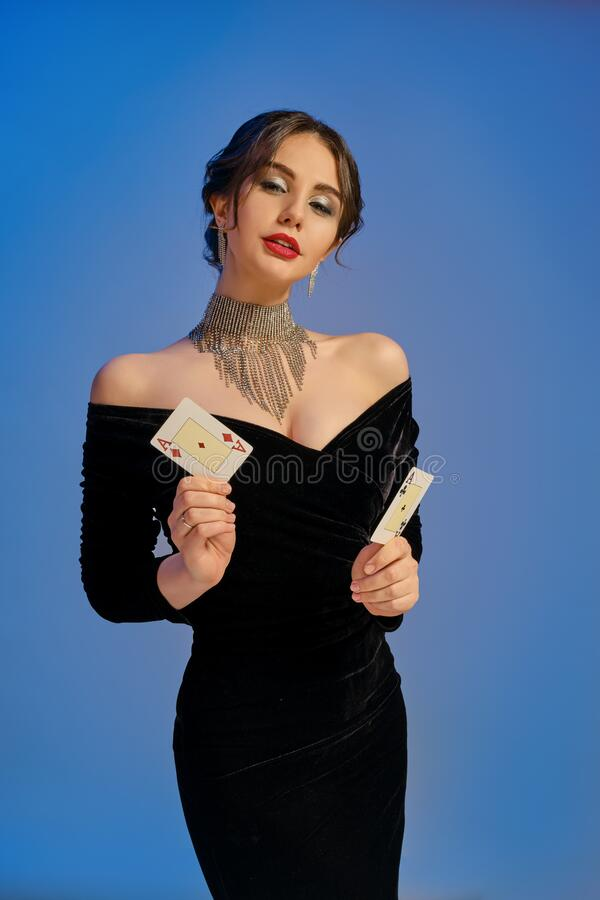 Free Brunette Lady With Bare Shoulders, In Black Dress And Shiny Jewelry. Showing Two Aces, Posing On Blue Studio Background Royalty Free Stock Images - 179392879