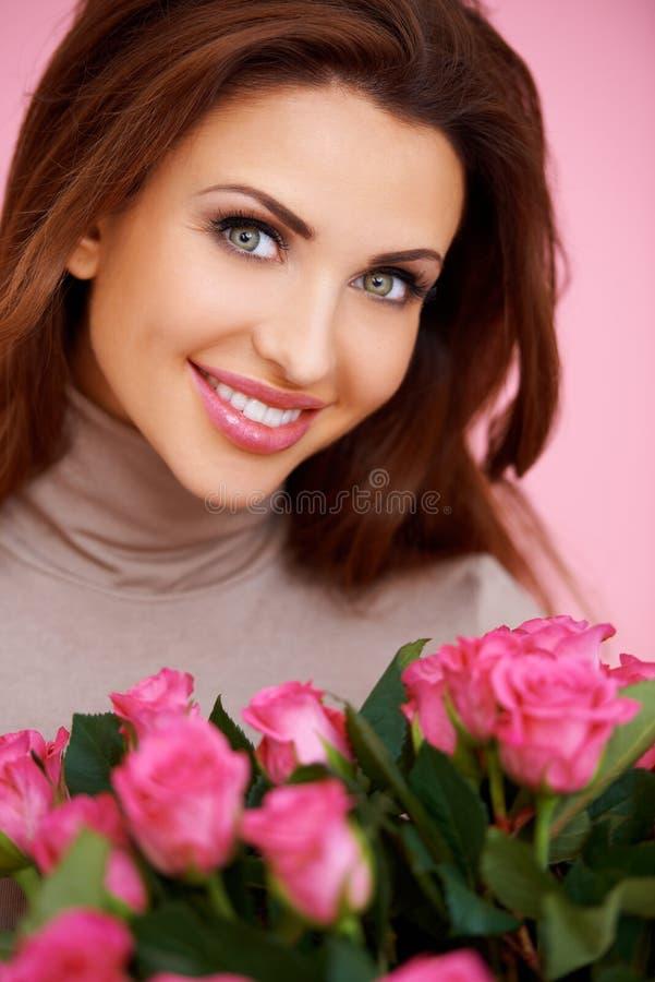 Brunette lindo com rosas cor-de-rosa fotografia de stock royalty free