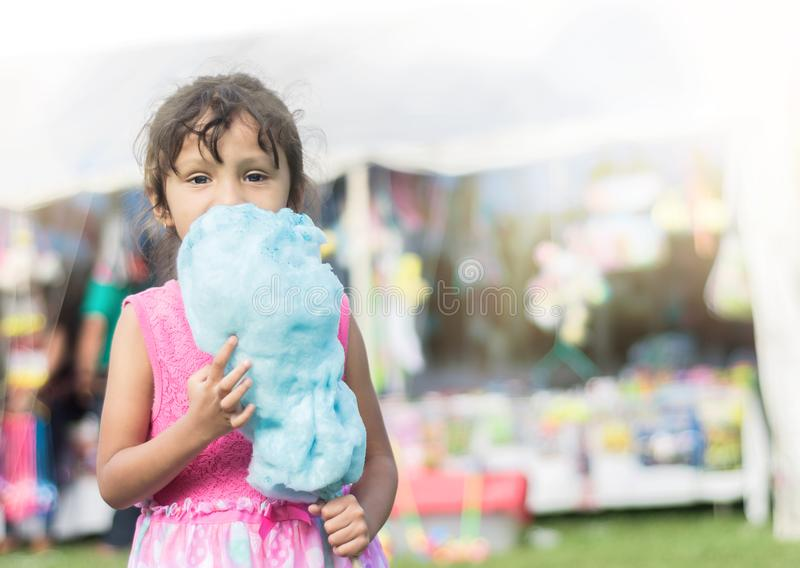 Brunette little girl at the town fair eating cotton candy royalty free stock images