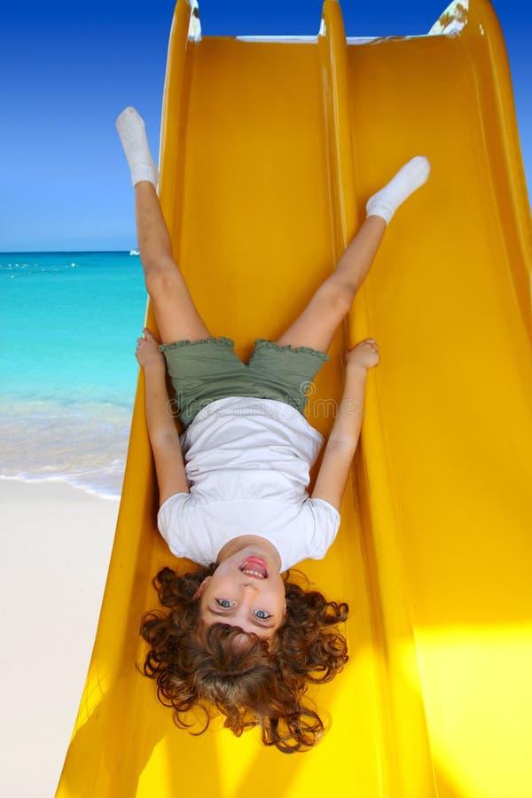 Brunette little girl upside down playground slide stock photos