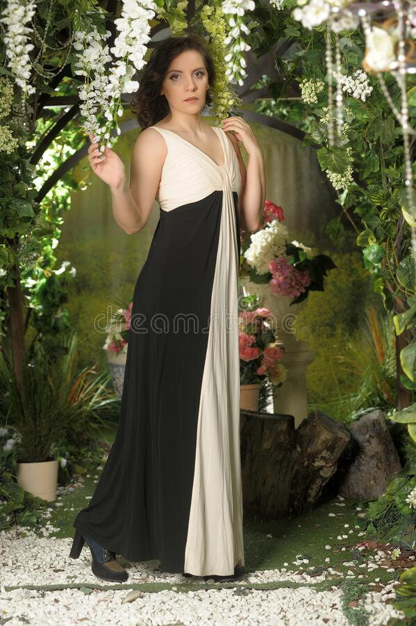 Brunette in a long evening dress in a greenhouse. Among flowers royalty free stock image